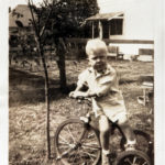 A young T. Boone Pickens rides his tricycle in his Holdenville, Oklahoma, back yard.