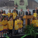 Neighborhood children join officials, including T. Boone Pickens (center clapping), for the formal September 16, 2010, dedication of the $6-million Walt Humann & T. Boone Pickens Community Center and Resource Center at Jubilee Park in South Dallas. Pickens provided funding for the center, a linchpin for revitalization efforts in the area by community organizations and the city.